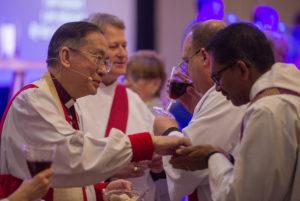 Archbishop Yong serving communion