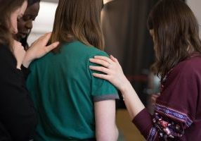 women-praying-laying on hands rosie-fraser-592594-unsplash (1)